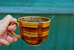 Brown filiżanka z herbatą w ręce Obrazy Stock