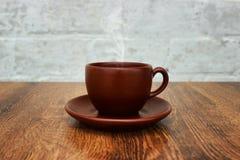 Brown filiżanka z spodeczkiem i aromatyczny dym na drewnianym stołowym zakończeniu obrazy royalty free