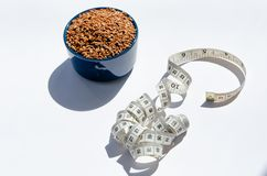 Brown flax seeds in blue ceramic bowl and centimeter on white background. Healthy weight loss concept royalty free stock image
