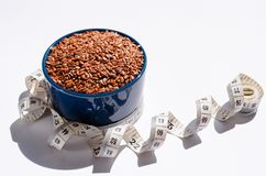 Brown flax seeds in blue ceramic bowl and centimeter on white background stock photography