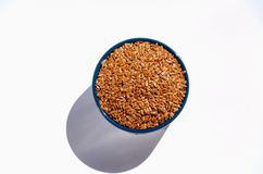 Brown flax seeds in blue ceramic bowl on white background royalty free stock photography