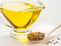 Brown flax seeds in spoon and flaxseed oil. In glass jug on trendy textured white concrete background. Flax oil is rich in omega-3 fatty acid royalty free stock photography