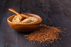 Brown flax seeds on spoon and flaxseed oil in glass jug on wooden table. Flax oil is rich in omega-3 fatty acid. stock image