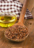Brown flax seeds on spoon and flaxseed oil Royalty Free Stock Photography