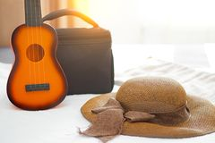 Brown floopy hat with ribbon, little guitar toy and suitcase bac royalty free stock images