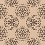 Brown floral ornament on beige background. Seamless pattern. Brown floral design on beige background. Seamless pattern for textile and wallpapers Royalty Free Stock Photography