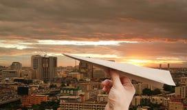 Brown-Flugzeugraketen-Papierin der hand Falte auf dem Stadthintergrund bei Sonnenuntergang stockbild