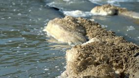 Brown foam on the surface of the river, caused by water pollution. Waste merges into the river.