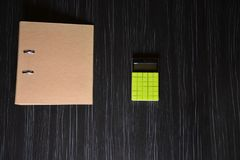 Brown folder with a green calculator. On the black office table stock photos