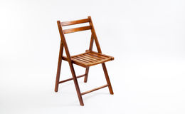 Brown Folding Chair on White. A brown, wooden, folding chair on a white background Royalty Free Stock Photo
