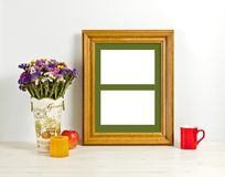 Brown frame mockup with field flowers in vase, apple, mug and ca Stock Images