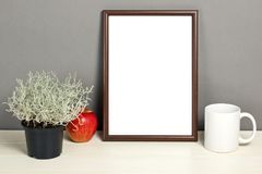 Brown frame mockup with plant pot, mug and apple on wooden shelf. Empty frame mock up for presentation design. Template framing for modern art Stock Photo