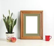 Brown frame mockup with plant pot, mug and apple on wooden shelf. Empty frame mock up for presentation design. Template framing for modern art Royalty Free Stock Photography