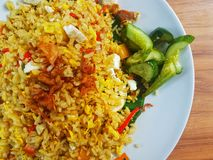 Brown fried rice with with chili,cucumber and fried onion in the white plate on the wooden table. Top view close up details. stock images