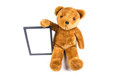 Brown fuzzy teddy bear holding a black frame Royalty Free Stock Photos