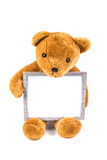 Brown fuzzy teddy bear holding a grey frame Royalty Free Stock Photos