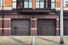 Brown garage doors for car parking in residential house Stock Photos