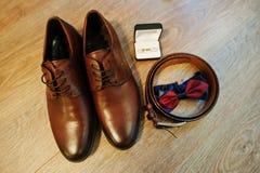 Brown garnissent en cuir des chaussures du ` s d'hommes avec la ceinture, le noeud papillon et les boutons de manchette positionn Images stock