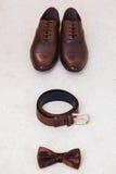 Brown garnissent en cuir des chaussures du ` s d'hommes avec la ceinture, noeud papillon Accessoires réglés de marié Photographie stock