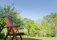Brown-Gartenstuhl-Frühlingsgarten-Baumhintergrund Lizenzfreie Stockfotos