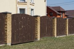 Brown gate and fence of wooden planks and bricks in the green grass. Brown gate and a fence of wooden boards and bricks in the green grass on the street royalty free stock photo