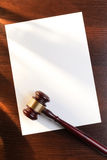 Brown gavel. Judges gavel on the table and a sheet of paper for the contract Stock Photography