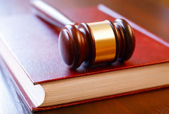 Brown gavel and law book. Closed on wooden table in the courtroom Royalty Free Stock Images