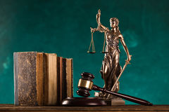 Brown gavel with statue of justice. Brown gavel with a brass band and statue of justice on wooden table Royalty Free Stock Photo