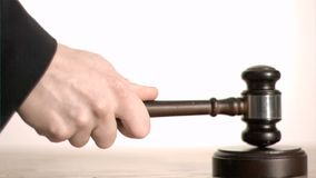 Brown gavel in super slow motion hitting a sound block Royalty Free Stock Photography