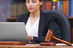 Brown gavel on wooden table and female lawyer. On background, close up view stock photos