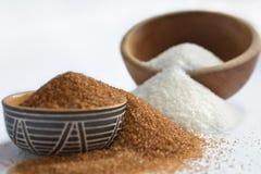 Brown gegen raffinierten Zucker. Zwei Varianten des Zuckers in den Schüsseln. Stockfotografie