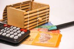 Brown-Geschenkbox auf Malaysia-Anmerkungen mit Taschenrechner und Stift Stockbild