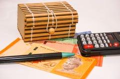 Brown-Geschenkbox auf Malaysia-Anmerkungen mit Taschenrechner und Stift Lizenzfreies Stockbild