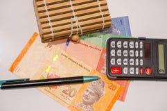 Brown-Geschenkbox auf Malaysia-Anmerkungen mit Taschenrechner und Stift Stockbilder