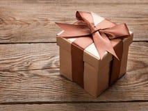 Brown-Geschenkbox mit einem Bogen auf dem alten Brett Getrennt über Weiß stockbild