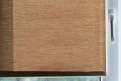 Brown-Gewebevorhänge auf weißem Plastikfenster Lizenzfreie Stockfotos