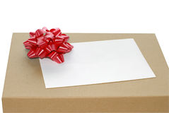 Brown gift box. Closeup of a plain brown gift box with a red bow and  blank envelope Royalty Free Stock Photos