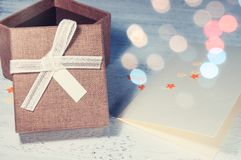 A brown gift box and a beige ribbon with a tag on a light backgr Stock Photo