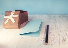 A brown gift box and a beige ribbon with a tag on a light backgr Stock Image