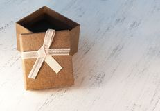 A brown gift box and a beige ribbon with a tag on a light backgr Royalty Free Stock Photography
