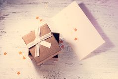 A brown gift box and a beige ribbon with a tag on a light background. A Christmas gift.Toning Royalty Free Stock Photo