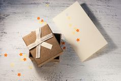 A brown gift box and a beige ribbon with a tag on a light background. A Christmas gift.Toning Stock Photography