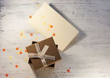 A brown gift box and a beige ribbon with a tag on a light background. A Christmas gift.Toning Royalty Free Stock Images