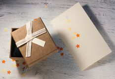 A brown gift box and a beige ribbon with a tag on a light background. A Christmas gift.Toning Royalty Free Stock Photos