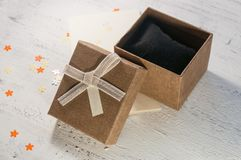 A brown gift box and a beige ribbon with a tag on a light background. A Christmas gift.Toning Royalty Free Stock Image