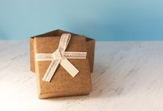 A brown gift box and a beige ribbon with a tag on a light backgr Stock Photos