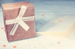 A brown gift box and a beige ribbon with a tag on a light backgr Stock Photography