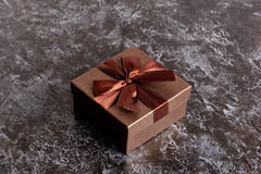 Brown gift box with bow on black table Royalty Free Stock Photo