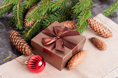 Brown gift box, Christmas bal, fir conesl and Green fir branches Royalty Free Stock Images