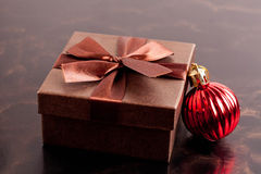 Brown gift box and Christmas ball on black background, closeup Royalty Free Stock Photos